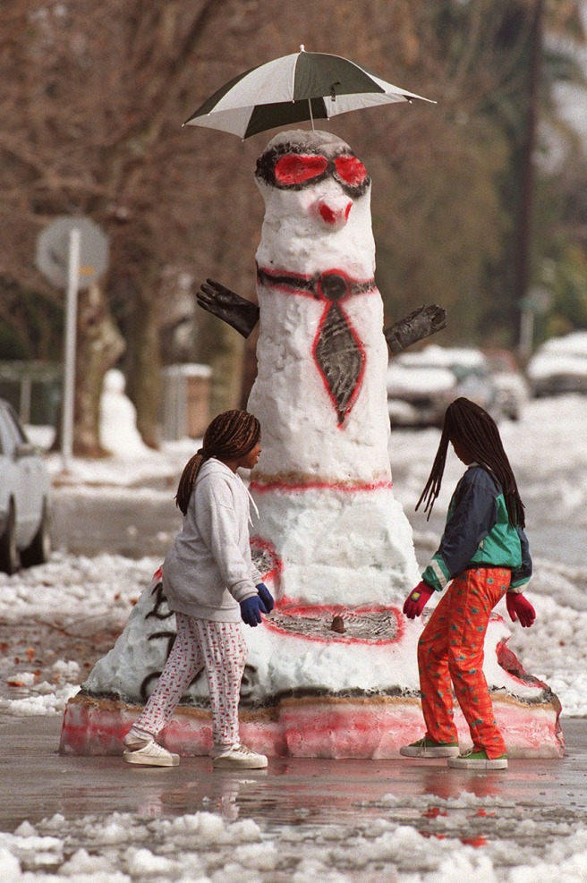 On Chester Place near L Street, Davina Williams, 11 (left) and Jamita Baker, 11, check out a 12-foot-tall snowman made Monday morning by their neighbors, Daniel Castellon Jr. and painted by his dad, Daniel Castellon.