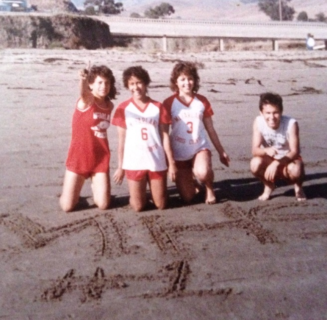 "At Morro Bay, Herlinda Gonzalez (6) wrote ""MHS #1"" in the sand. Silvia Diaz is #3, her brother Raul is at right. (Working to get name of runner at left.) Picture was taken with Raul's camera by a team member."
