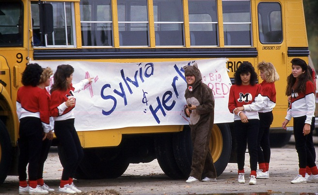 This photo, from the 1986 Central section championship meet, shows the cheerleaders, including Dolores Plata (second from left) decorating a bus in memory of Sylvia and Herlinda. It was shot by Casey Christie.