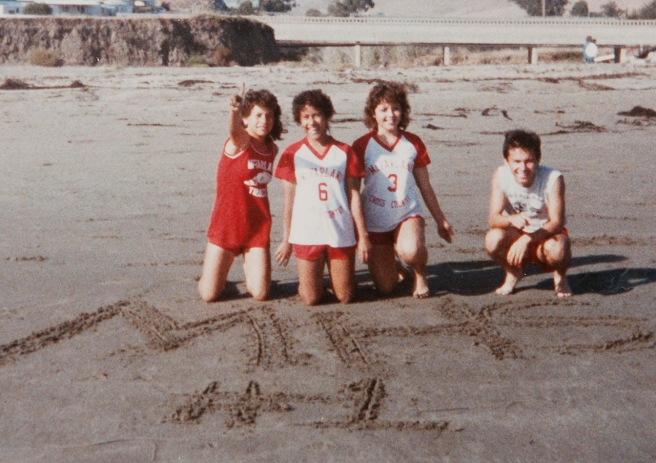 "During the beach trip in 1985 when coach Jim White took the teams to Cayucos following the Santa Maria Invitational, Herlinda Gonzalez wrote ""MHS #1"" in the sand. From left is Herlinda, Delfina Herrera, Sylvia Diaz and her brother, Raul Diaz. The photo was taken with Raul's camera by a teammate and are the only known images of the real beach trip depicted in the movie ""McFarland USA.""."